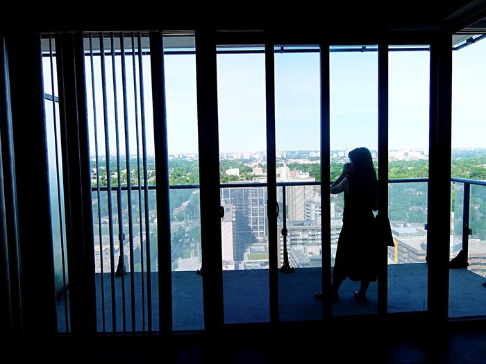 Balcony view Condominium Condo City Life Cityscape Speaking On The Phone Silhouette Window Glass - Material Real People Silhouette Standing Lifestyles Women Architecture Transparent Looking At View The Traveler - 2018 EyeEm Awards The Architect - 2018 EyeEm Awards EyeEmNewHere