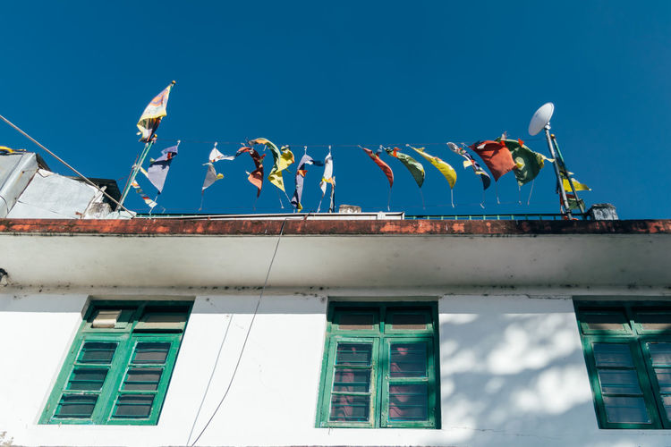 Low angle view of flags on building against blue sky