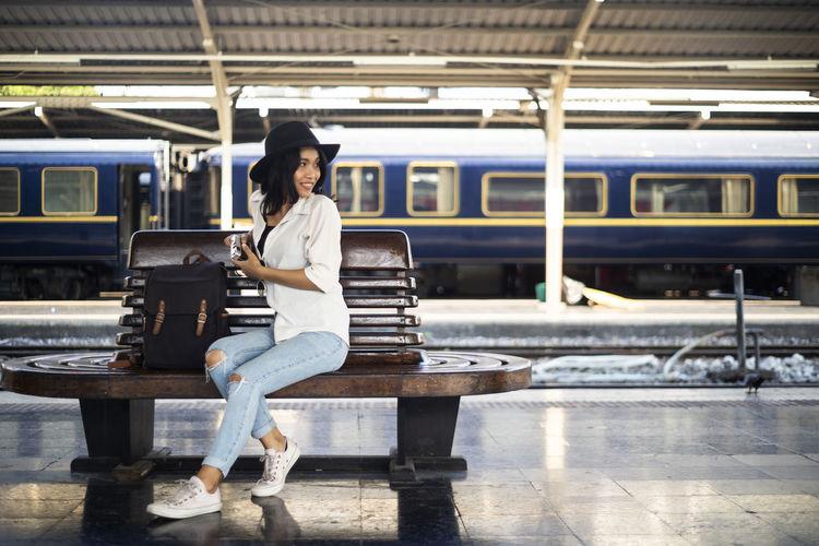 Portrait of woman sitting on railroad station platform