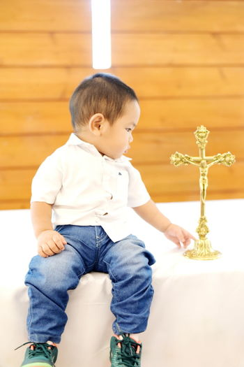 Baby boy looking at cross while sitting on table