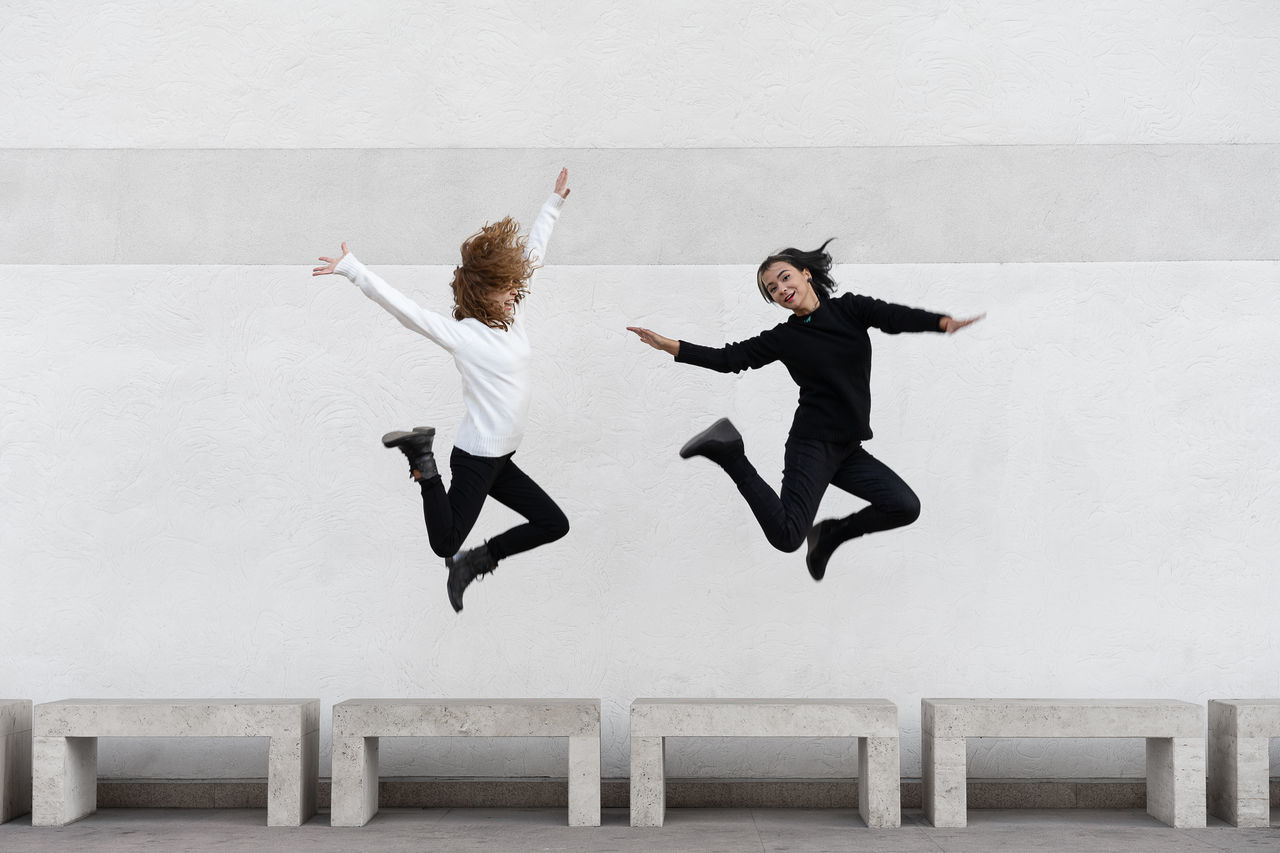 Lesbian couple jumping against wall