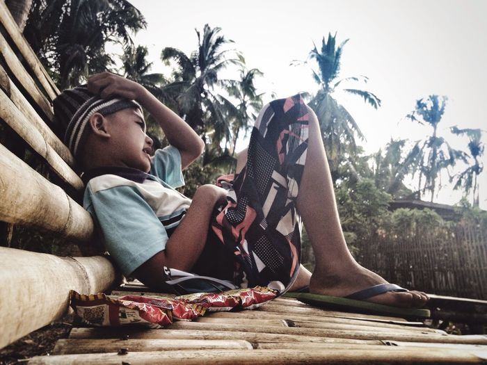 Side view of boy resting on bamboo bench against sky
