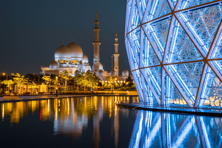Reflection of illuminated building in water at night