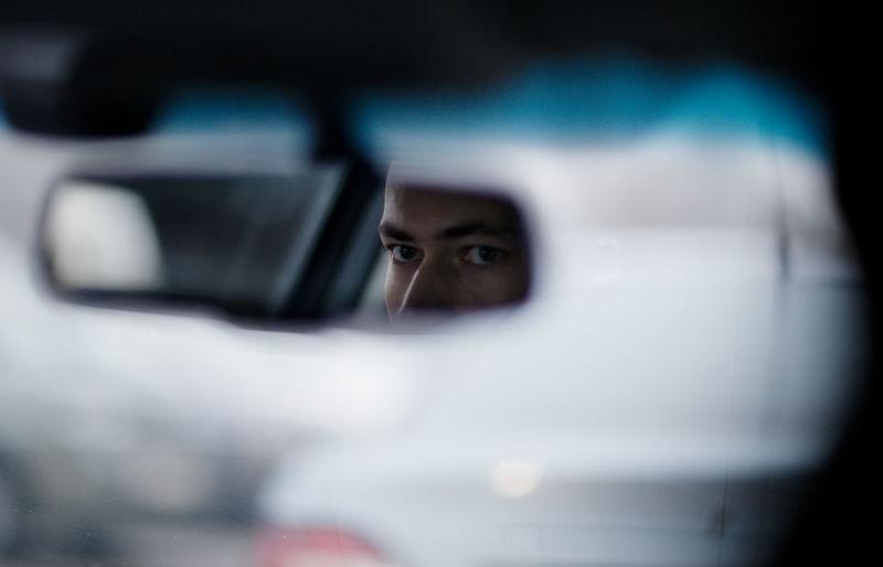 Reflection of man mirror at car