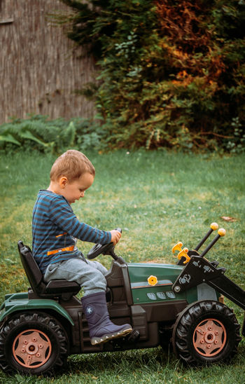 Side view of boy sitting by plants