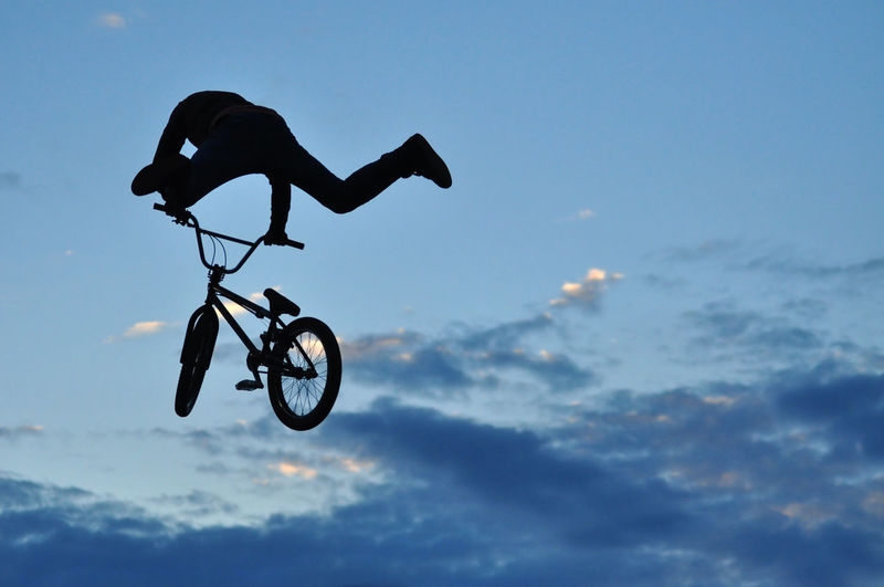Low Angle View Of Silhouette Man With Bicycle Against Sky