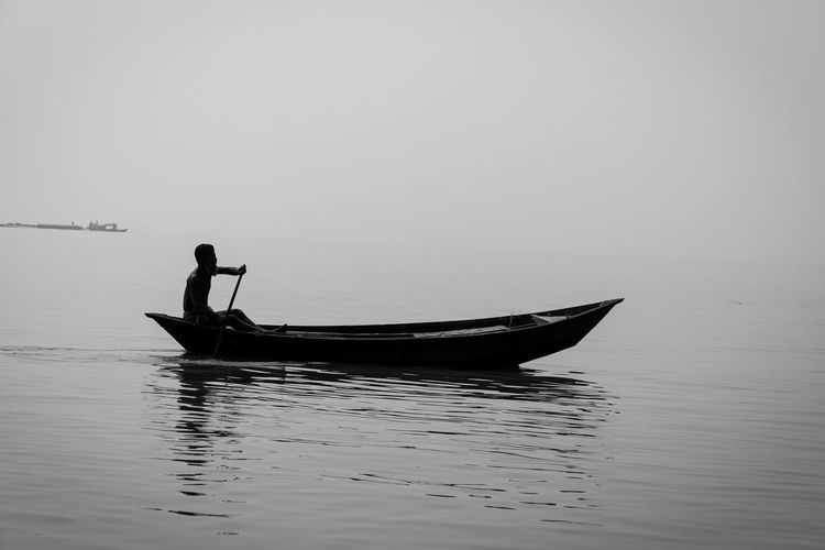 Silhouette man in boat on sea against sky
