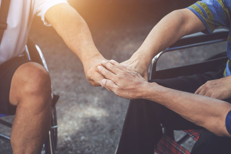 Cropped image of people on wheelchair stacking hands together