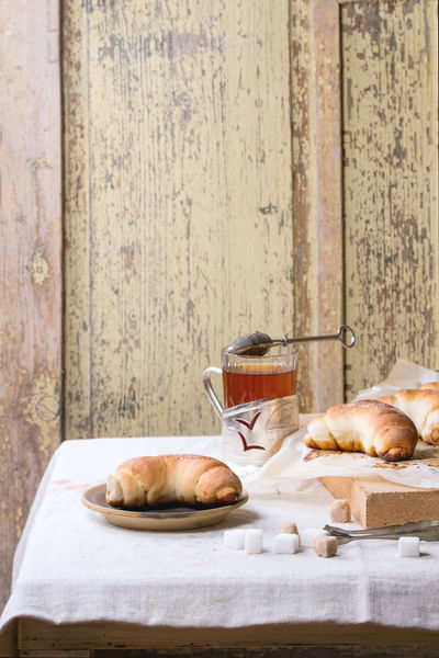 Cup of hot tea with fresh homemade baked bagels on ceramic plate and baking paper over light gray tablecloth Baked Bakery Baking Paper Bread Bread Rolls Comfort Food Crescent Day Food Food And Drink Fresh Baked Bread Glass Homemade Bread Homemade Food Meal Plate Rolls Stone Sugar Sweet Food Table Tablecloth Tea Tea Time White