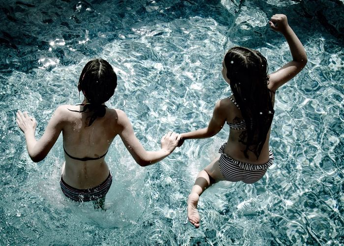 High Angle View Of Girls Jumping In Swimming Pool On Sunny Day