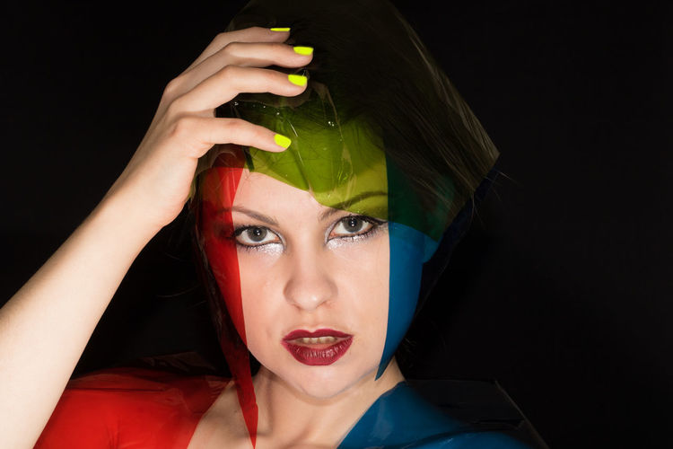 Portrait of fashion model with colorful plastic against black background