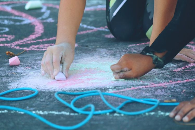 Cropped Image Of Friends Drawing With Chalk On Footpath