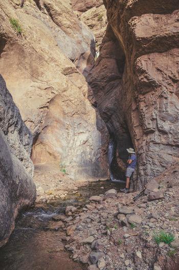 Rear view of man walking on rock