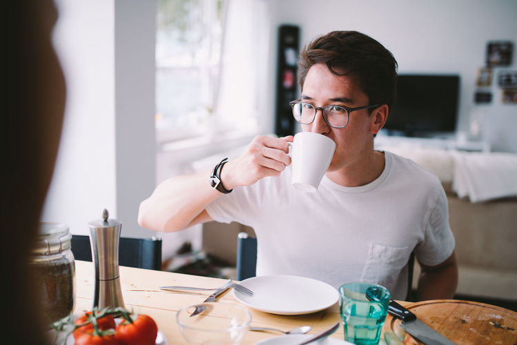 Man Drinking Coffee Cup On Table At Home