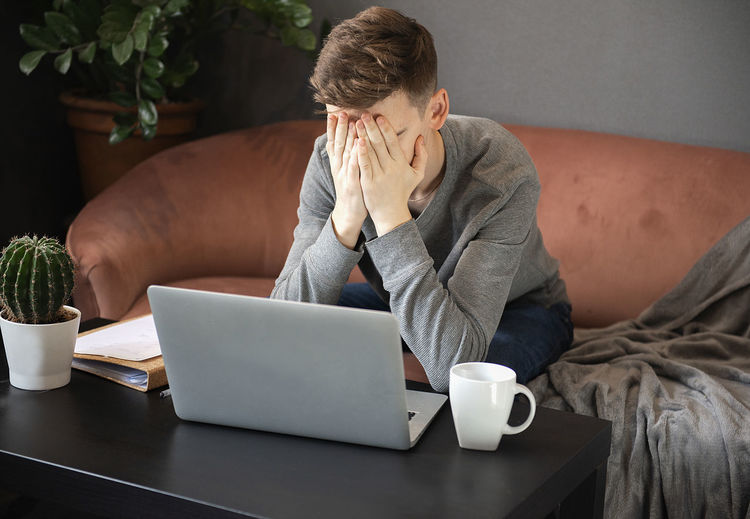 Frustrated young man student looking exhausted and covering his face with hands  sitting at laptop