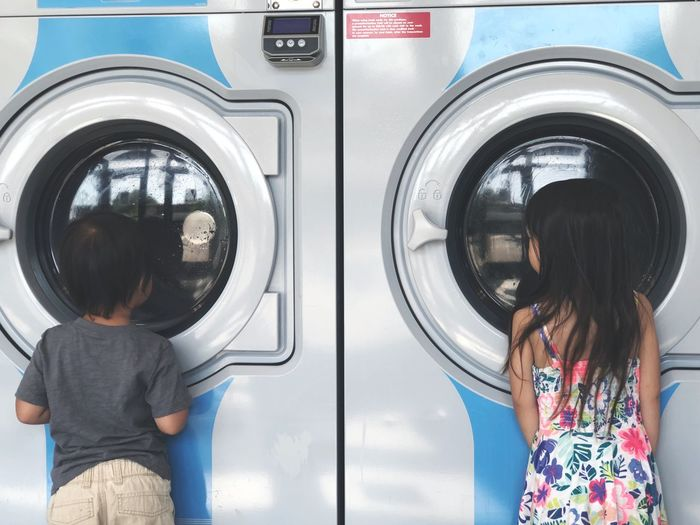 Rear view of siblings standing against washing machines at laundromat
