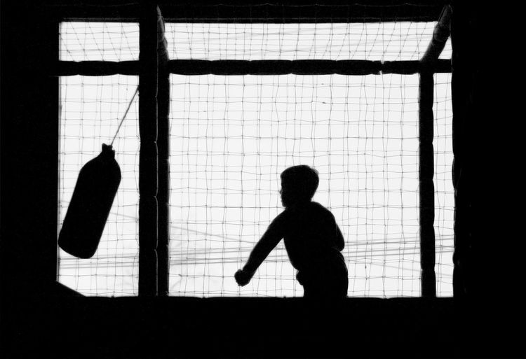 Silhouette Boy Punching On Bag Hanging By Window