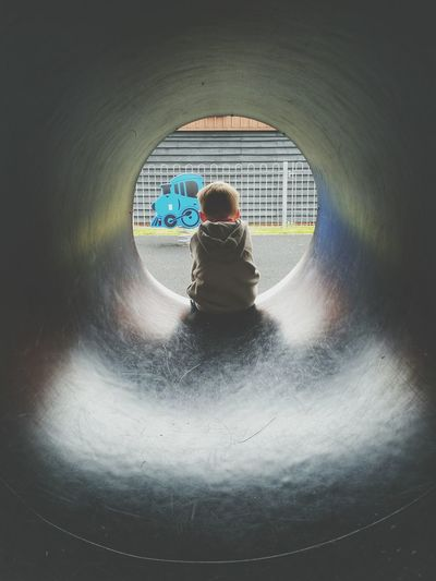 Rear view of boy sitting in tunnel slide