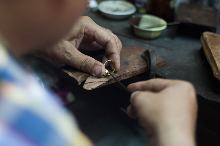 Midsection of man working on jewelry in workshop