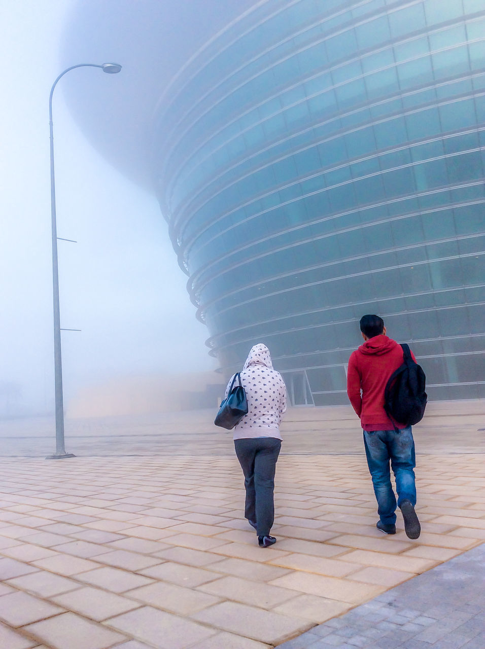 Full Length Rear View Of Man And Woman Walking Against Building During Foggy Weather