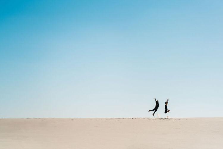 People walking on desert against clear sky