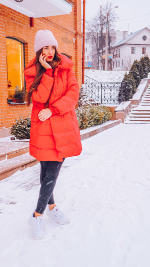 Beautiful happy smiling woman on the street in warm red winter coat on Christmas time on snowing. Winter Cold Temperature Warm Clothing Snowing Smiling Christmas Wintertime Woman Power women around the world EyeEm Best Shots EyeEm Colorful! Fashion Stories Red Lipstick Snow One Person Clothing Full Length Real People Young Adult Standing Adult Architecture Leisure Activity Day Lifestyles Young Women Women Scarf Outdoors