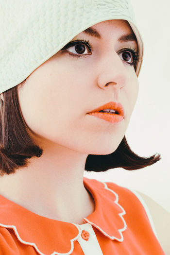 Close-up of thoughtful woman looking away against white background