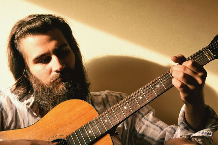 Bearded man playing guitar against wall at home