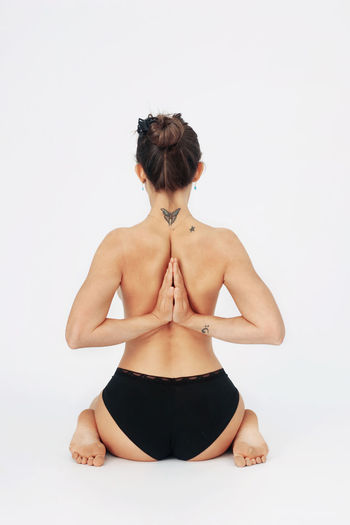 Rear view of woman sitting against white background