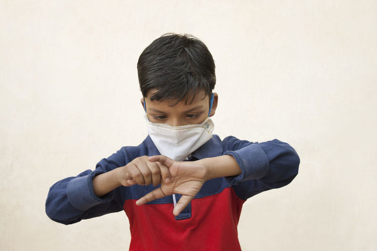 Close-up of boy wearing flu mask holding finger standing against wall