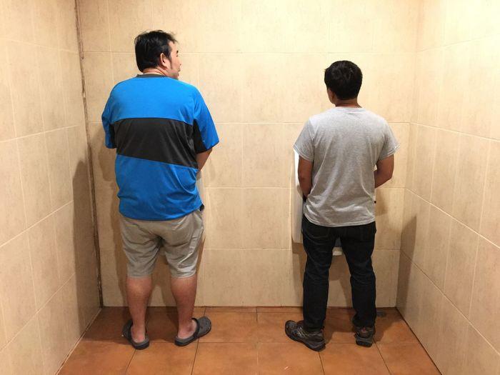 Rear view of men urinating in public bathroom