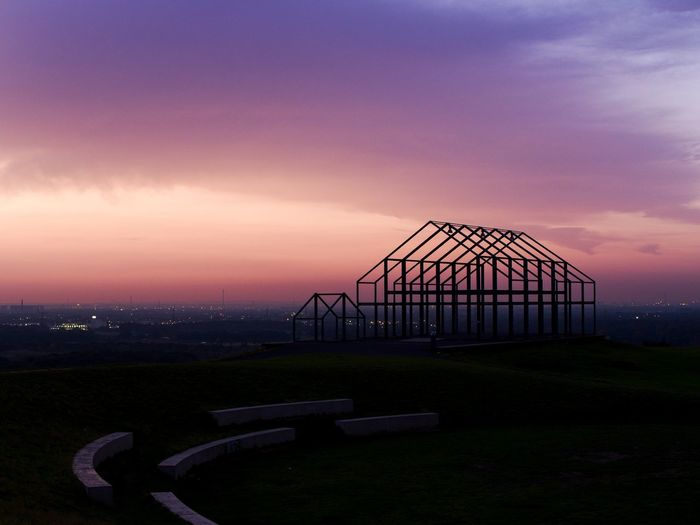 Built structure on field against sky at sunset