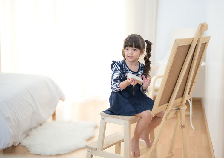 Full length of girl sitting on seat at home