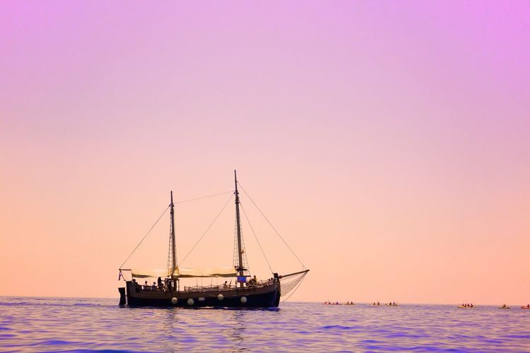 Ship Sailing In Sea Against Clear Sky During Sunset
