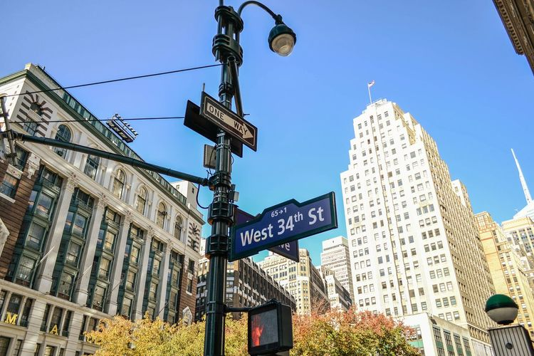 Low Angle View Of Direction Sign Against Modern Buildings In City