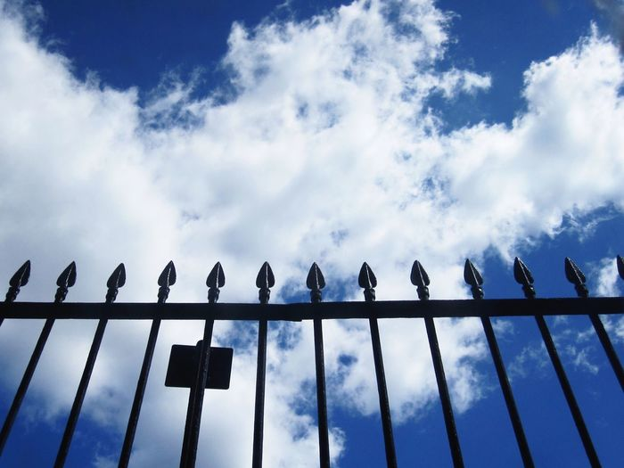 Low angle view of railing against cloudy blue sky