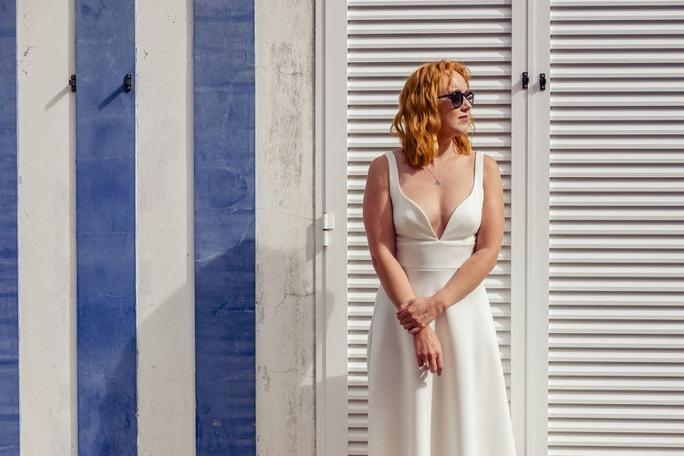 Woman in dress and sunglasses standing against wall