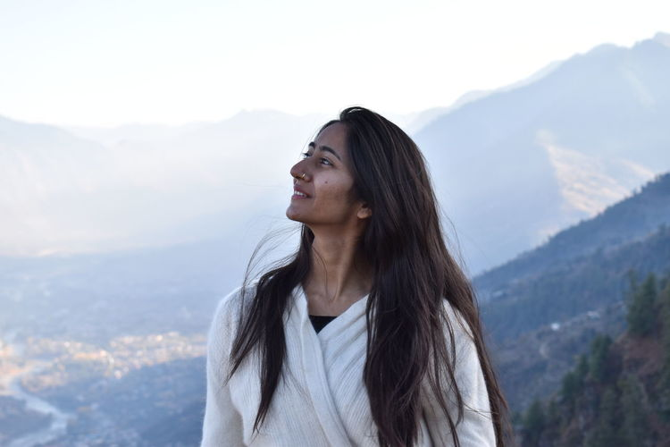 Beautiful young woman looking away against mountains