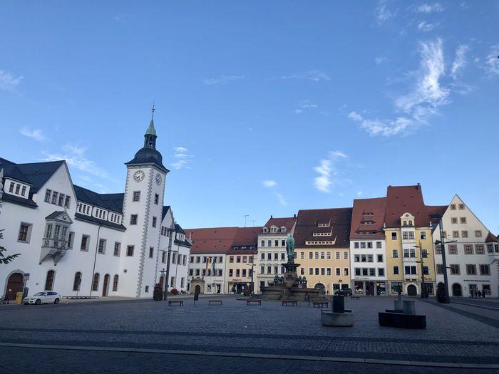 View of buildings in town against blue sky