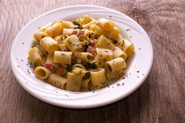 Rigatoni pasta with pancetta and zucchini Dish Zucchini Bacon Bowl Cheese Close-up Food Food And Drink Freshness Garnish Healthy Eating High Angle View Indoors  Italian Food No People Pasta Plate Ready-to-eat Serving Size Still Life Table Temptation Vegetable Wellbeing Wood - Material