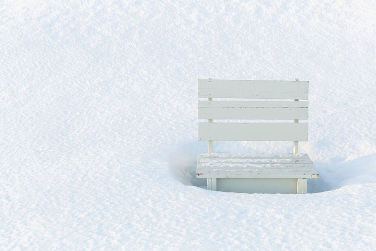 High Angle View Of Empty Bench On Snow Covered Field