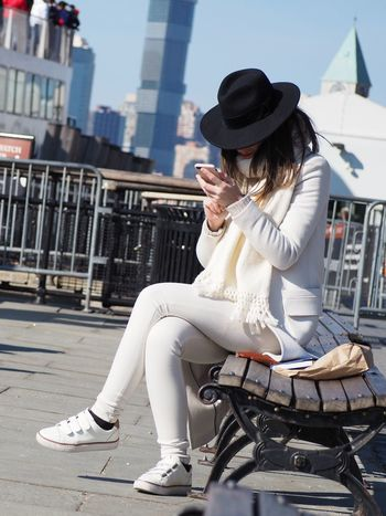 A woman dressed in white wearing a black hat using her smartphone America New York Sunshine Sunny Wireless Connection Connected Phone Smart Phone Cell Phone  Bench Young Colour Your Horizn White Woman Hat Wireless Technology Casual Clothing Sitting Fashion Portable Information Device Mobile Phone One Person Outdoors Day Young Adult Technology City Adult One Young Woman Only The Street Photographer - 2018 EyeEm Awards The Portraitist - 2018 EyeEm Awards