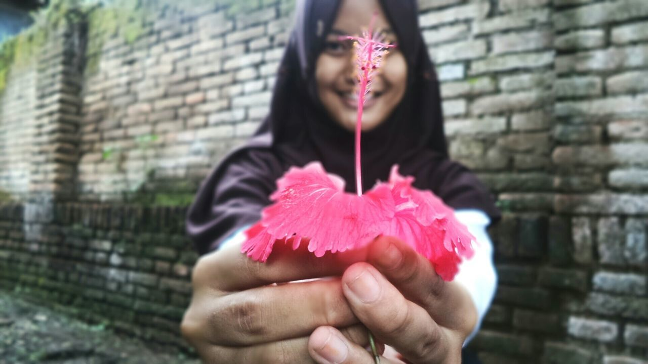 Woman Showing Hibiscus Flower Against Brick Wall