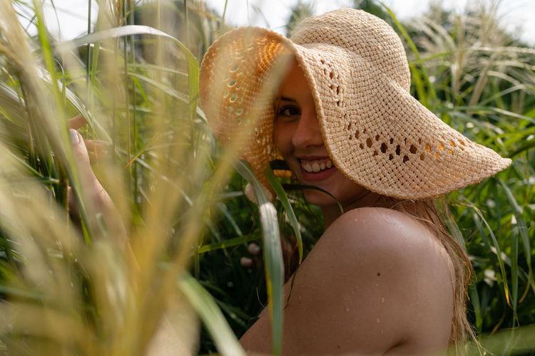 Portrait of woman wearing hat standing by plants