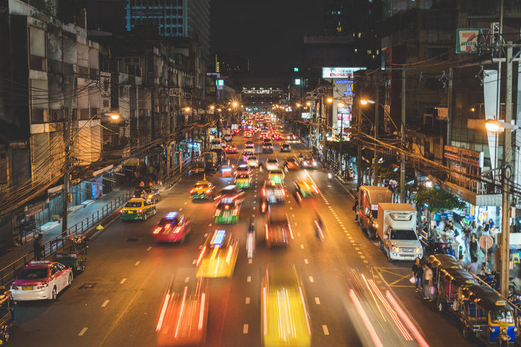 Blurred motion of cars on city street amidst buildings at night