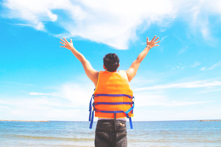 Rear view of man with arms raised standing at beach against sky