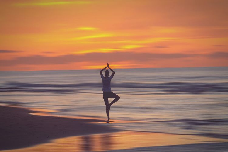 Woman doing yoga at beach during sunset