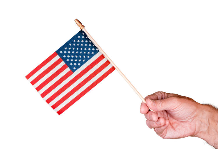 Close-up of hand holding flag against white background