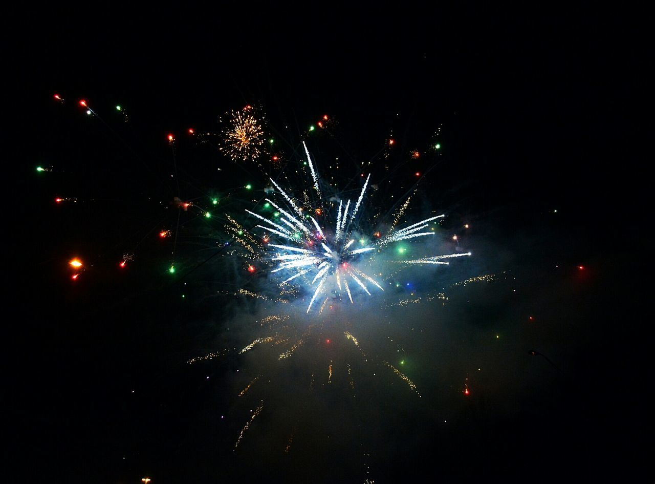celebration, firework display, night, firework - man made object, event, exploding, arts culture and entertainment, illuminated, long exposure, low angle view, glowing, smoke - physical structure, outdoors, no people, blurred motion, motion, multi colored, sky, firework