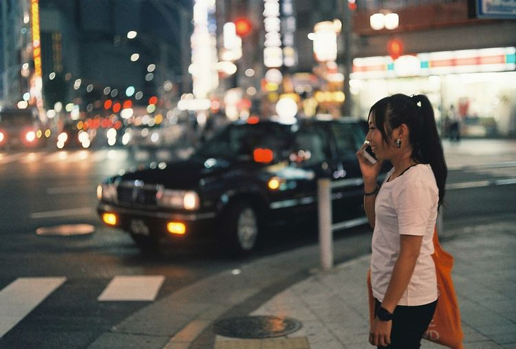 Side view of young woman talking on mobile phone while standing on street at night